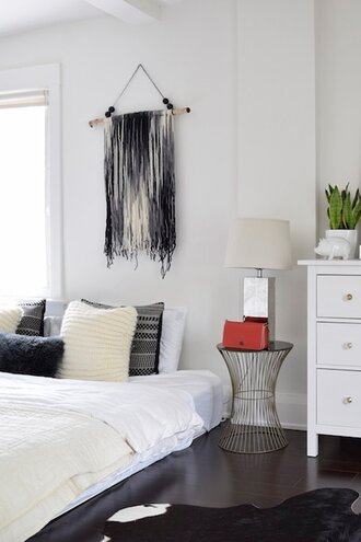A Minimalist White Bedroom With Black And White Macrame Hanging Above The  Bed.