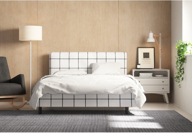 Picture of bedroom with large, upholstered bed up against the wall.