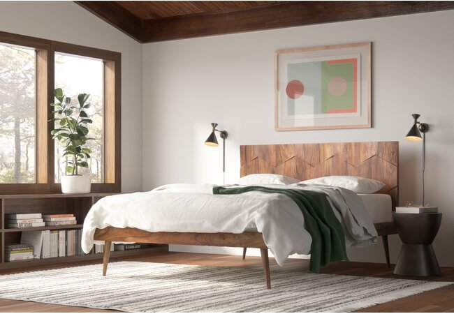 Picture of bedroom with large bed against the center of the wall.