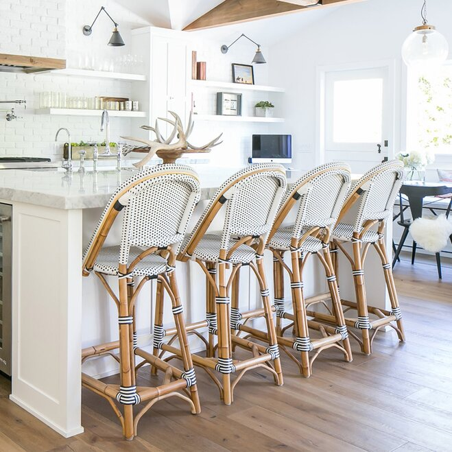 An All White Kitchen With Marble Countertops And A Long Breakfast Bar With  Four French