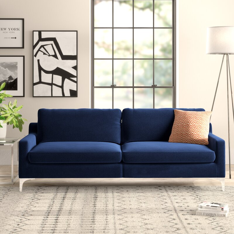 a picture of a blue couch with one accent pillow, a side table with a plant, and a stack off books upon the carpeted floor