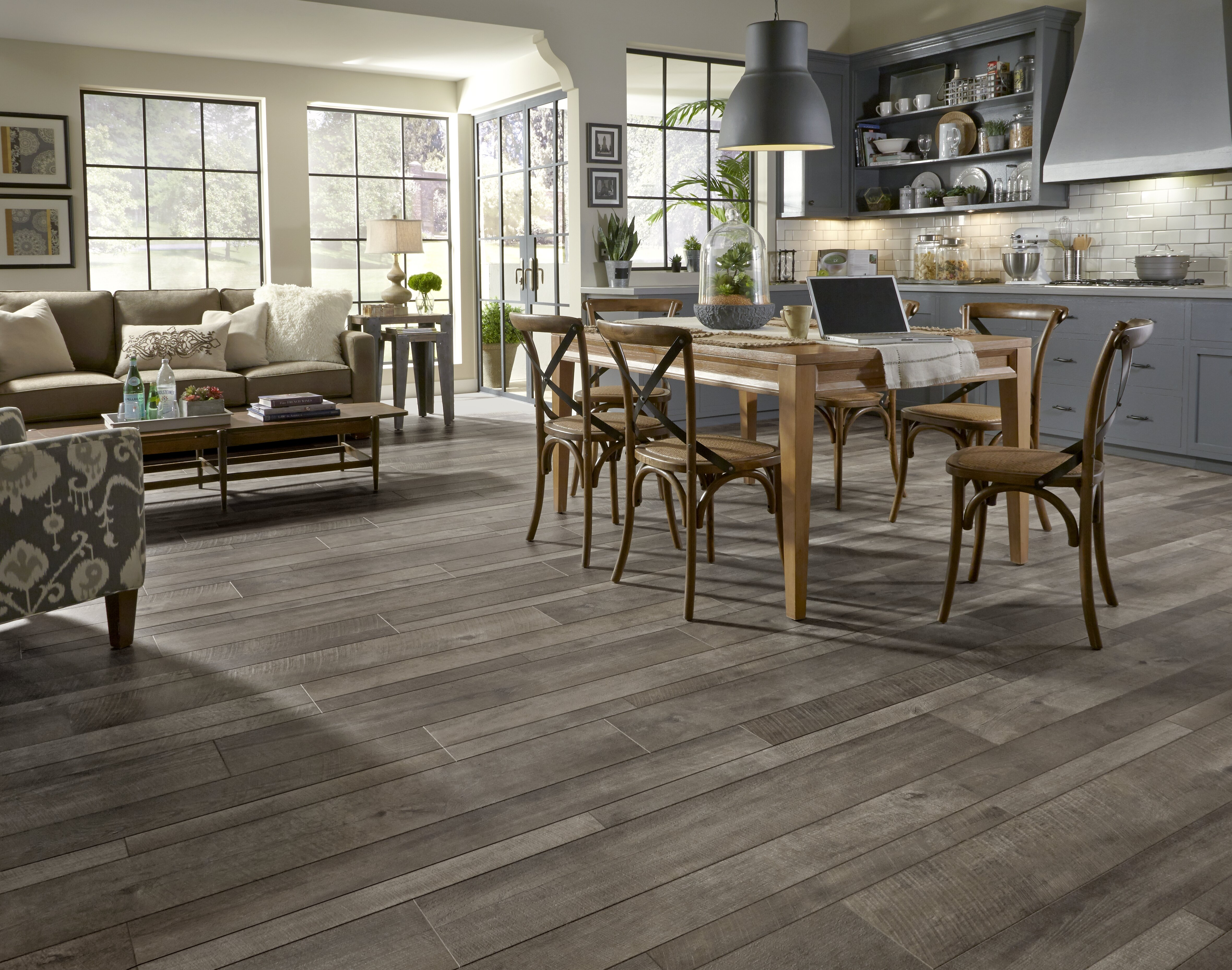 Oak laminate flooring in a gray kitchen with a wooden dining area and tan couches