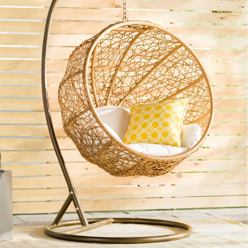 round hanging basket chair made of wicker with yellow cushion