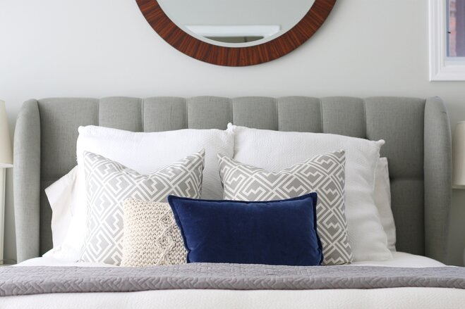 A Grey Linen Headboard With Large Round Wooden Mirror Hung Above