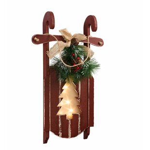 rustic wooden sled with lighted holiday cutout design