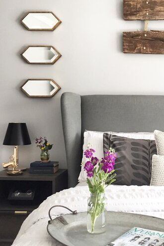 A Grey Linen Headboard With 3 Pee Identical Mirrors Hung Above The Nightstand