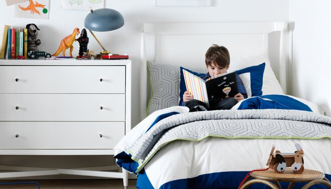 Boy Reading A Book In Bed