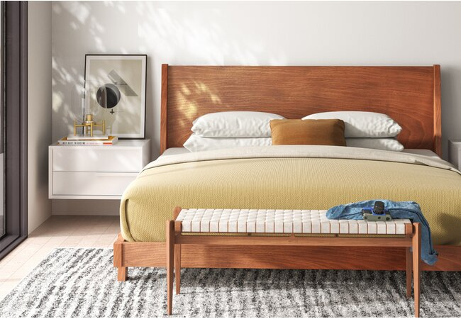 Picture of bedroom with large, wooden bed against the center of the wall.