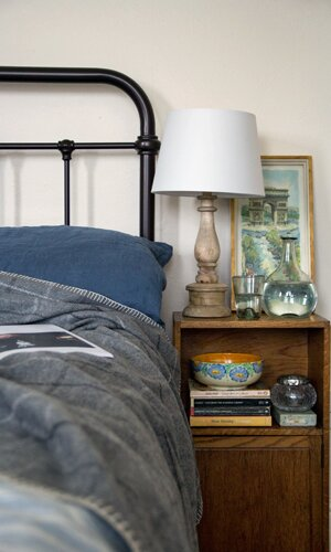 A bed with a cuddly grey throw blanket, wooden bedside lamp, water glasses and vase.