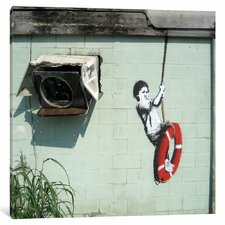 Boy on Life Preserver Swing by Banksy Photographic Print on Wrapped Canvas